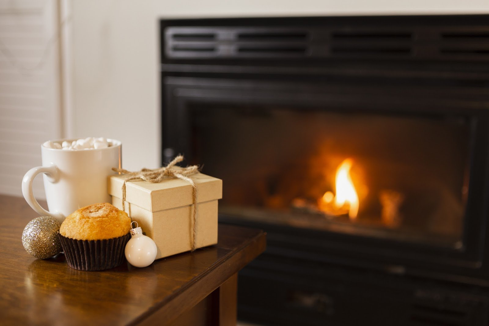 hot-chocolate-muffin-and-small-gift-in-front-of-lit-gas-fireplace-insert