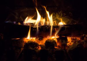 wood logs on fire in a fireplace coating the inside of the chimney with creosote