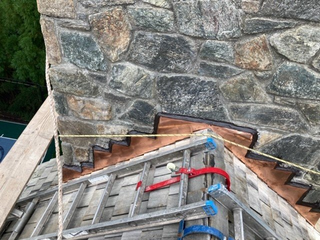 ladders and tools on a roof in front of a chimney during chimney flashing repairs