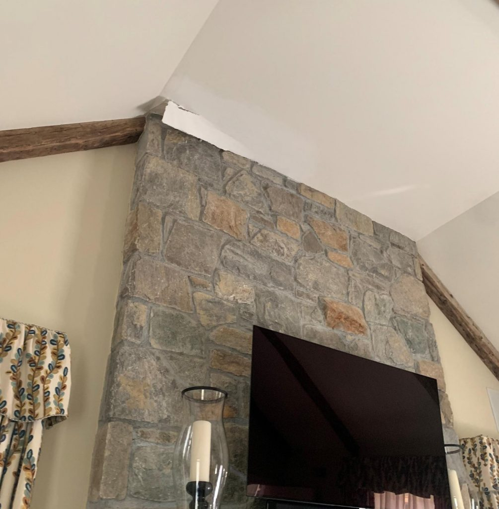 water damage on a living room ceiling from leaking chimney flashing