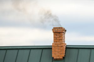 smoke rising from the top of a chimney that does not have chimney downdraft issues