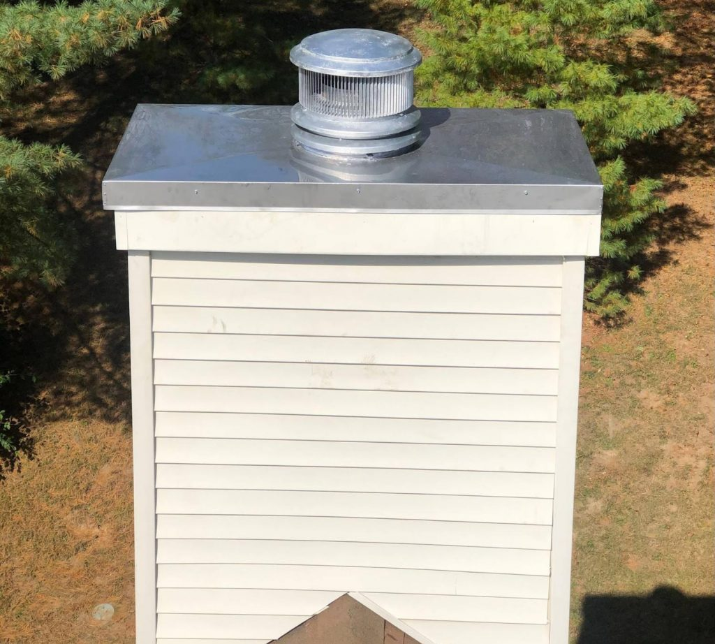 A newly installed metal chimney chase cover on a chimney chase clad with vinyl siding