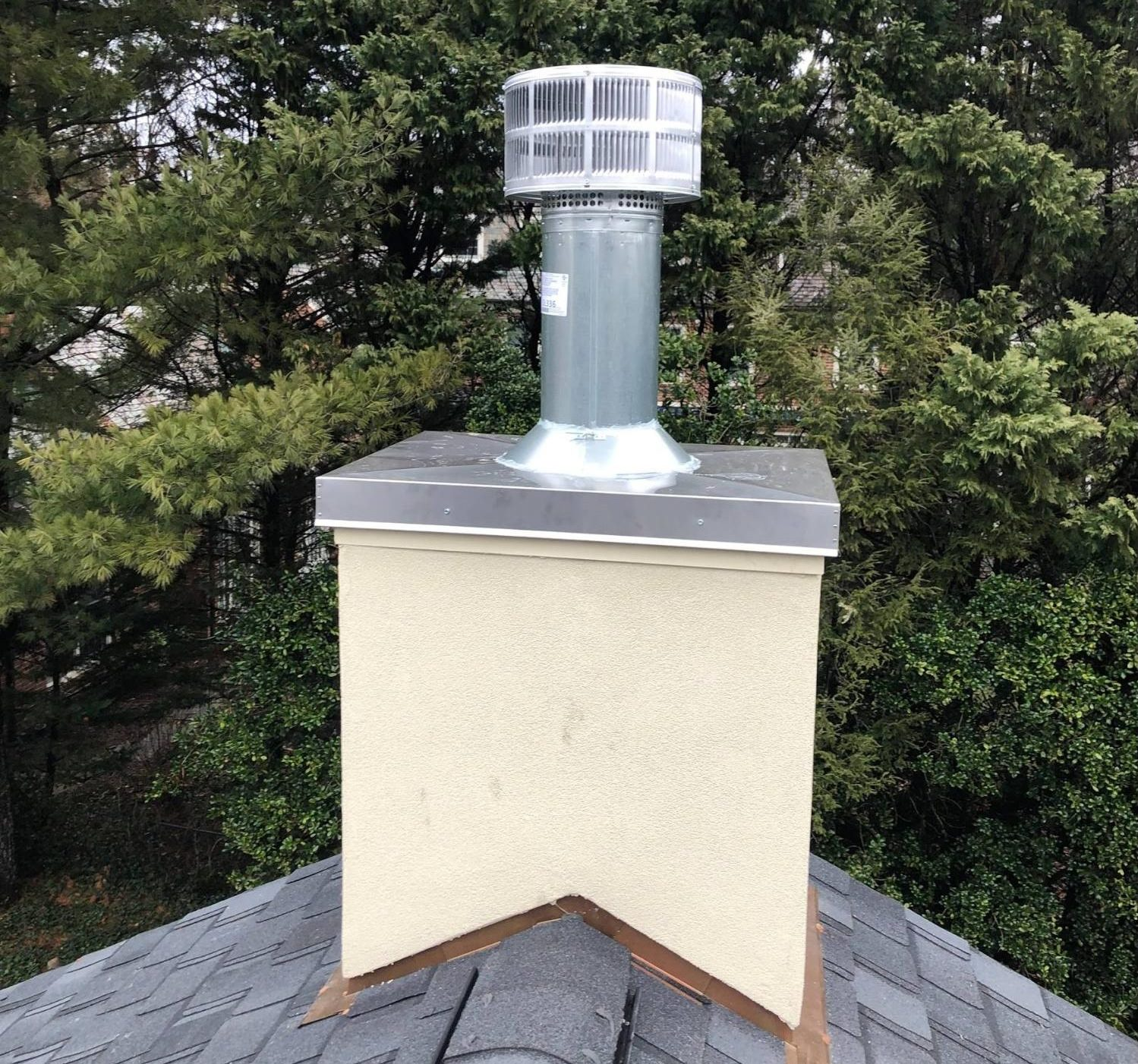 A plaster chimney chase with a metal chase cover and tall exhaust pipe