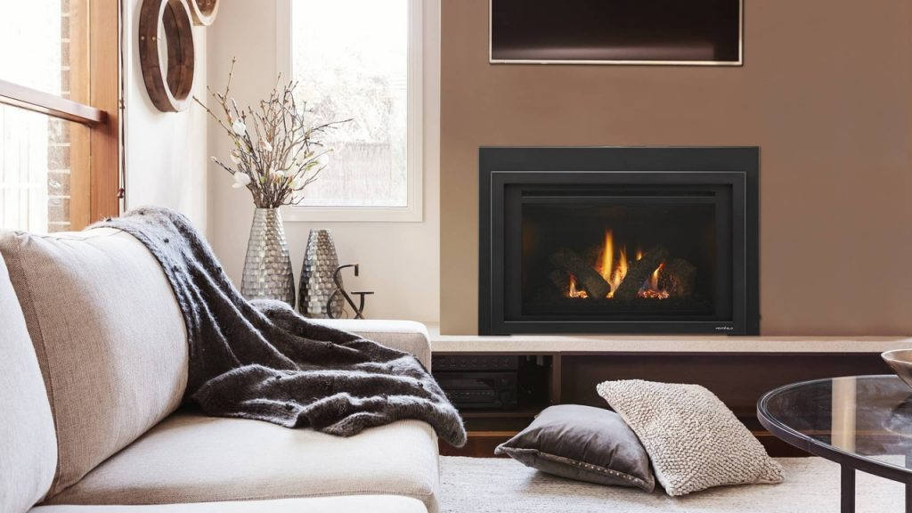 A comfortable living room with a fire burning in a gas fireplace. Converting from a wood burning fireplace to gas can help with fuel efficiency and keep your home warm.