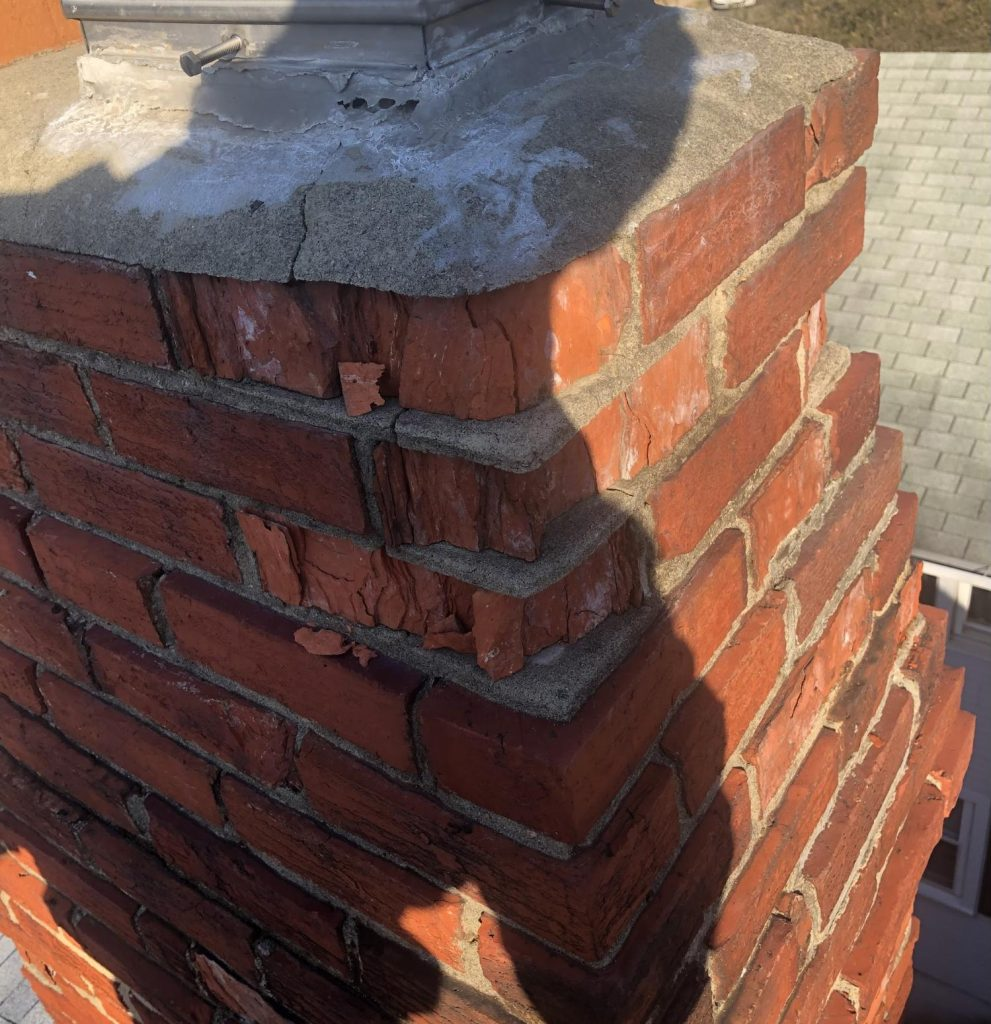 Close up shot of pieces of red brick crumbling and falling out of mortar joints in an old chimney.