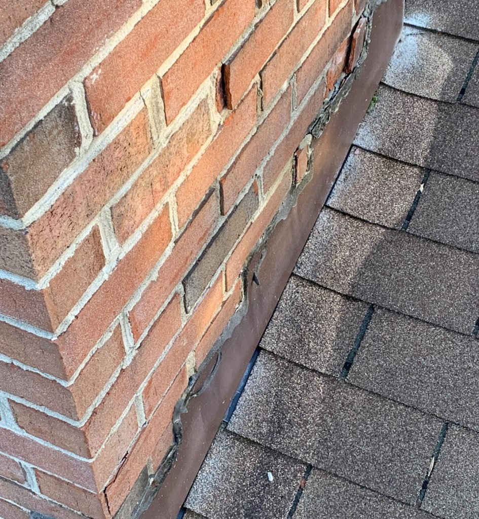 A close up shot of spalling bricks in a chimney close to the chimney flashing. Spalling bricks allow moisture into the brick which defeats the purpose of the chimney flashing and makes it less effective at preventing water damage to the home.