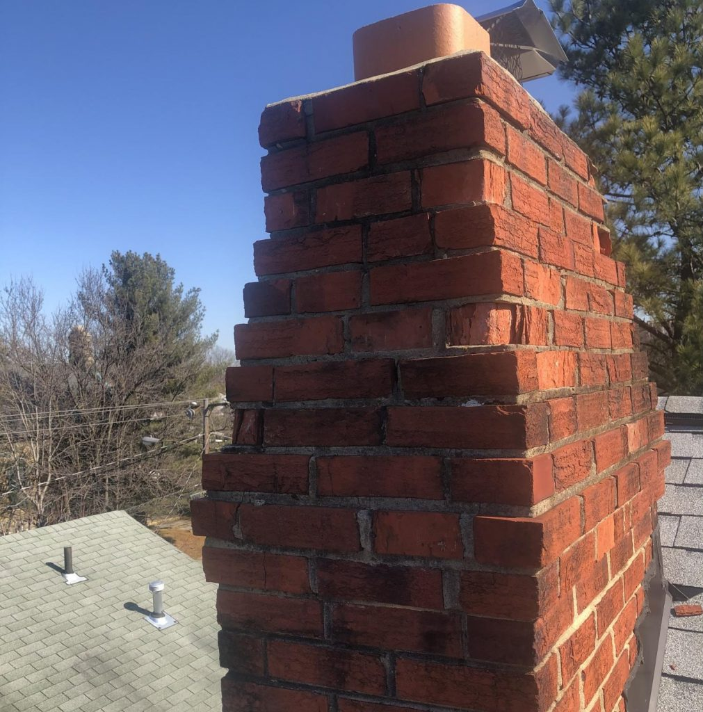 A brick chimney which is at risk of collapse due to a number of spalling bricks.