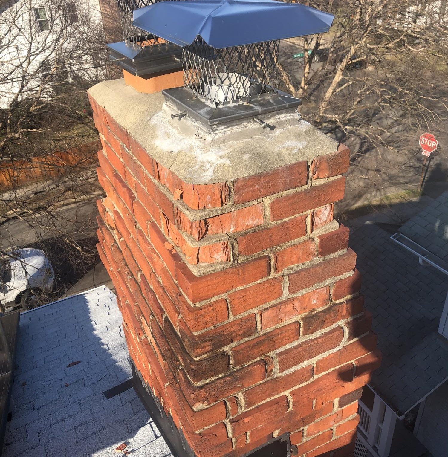 A masonry chimney with many spalling and crumbling bricks. Spalling bricks present a danger to the structural integrity of a house and to the safety of homeowners.