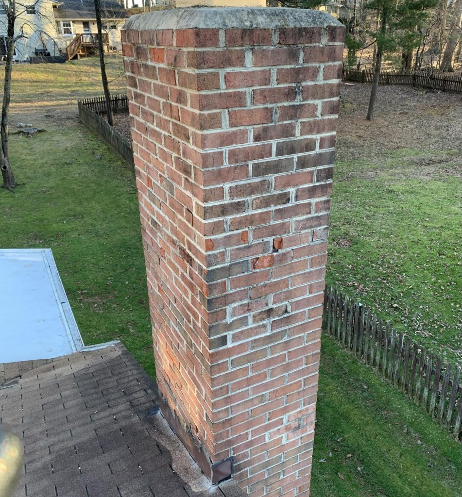 A tall brick chimney with a number of spalling bricks. When bricks start to crack and crumble, they should be replaced to prevent further damage to the chimney and home.